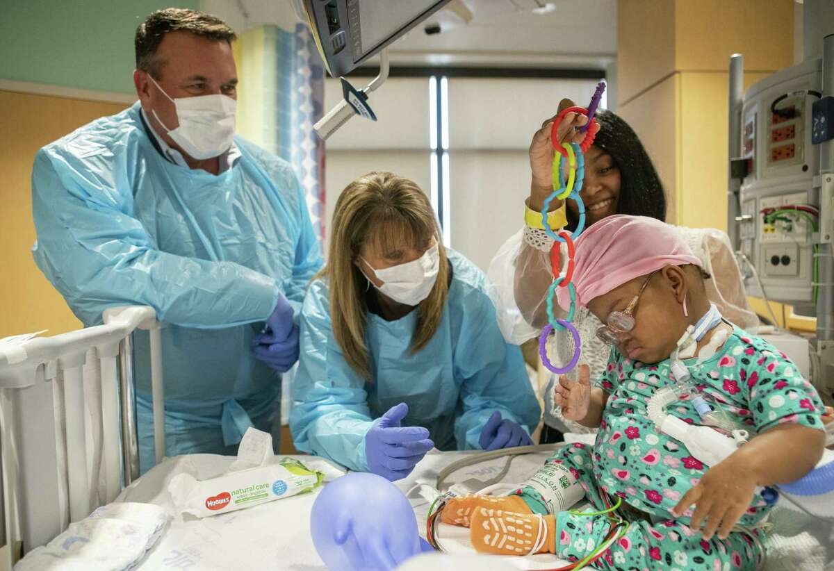 Ross Witty, from left, and Cheryl Witty visit with Rebecca Jones and her 1-year-old daughter, Brooklyn, inside the transitional ICU at Texas Children's Hospital in Houston, Thursday, May 16, 2019.