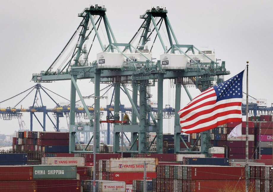Chinese shipping containers are stored beside a U.S. flag after they were unloaded at the Port of Los Angeles in Long Beach, California on Tuesday. Global markets remain on red alert over a trade war between the two superpowers China and the US, that most observers warn could shatter global economic growth, and hurt demand for commodities like oil. Photo: MARK RALSTON /AFP /Getty Images / AFP or licensors