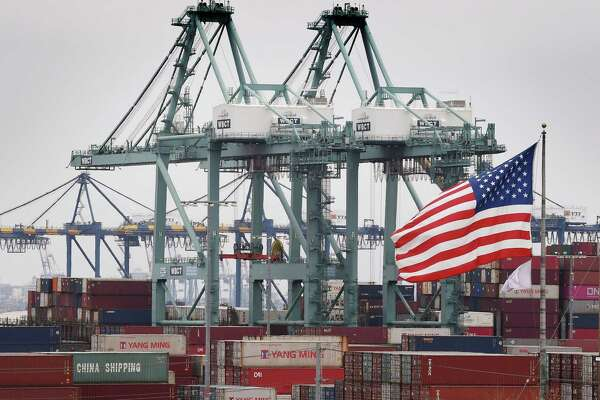 Chinese shipping containers are stored beside a U.S. flag after they were unloaded at the Port of Los Angeles in Long Beach, California on Tuesday. Global markets remain on red alert over a trade war between the two superpowers China and the US, that most observers warn could shatter global economic growth, and hurt demand for commodities like oil.
