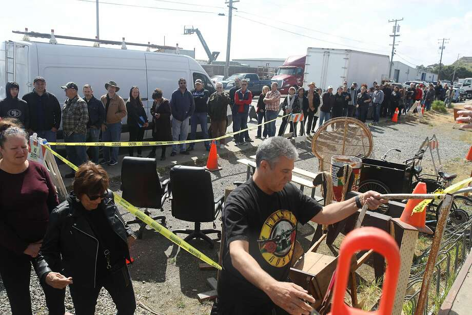 """Above: A line of people enters the Acme Scenery and Prop House sale run by YES Company on Friday, May 17, 2018 in Brisbane, Calif. Left: Kevin """"A.J."""" Black (right), proprieter the YES Co., tallys up the purchase of Bridget Wylie, of Redwood City and propmistress for Broadway by the Bay and Pied Piper Players, at the Acme Scenery and Prop House sale run by YES Company on Friday, May 17, 2018 in Brisbane, Calif. """"They're going to have a good home"""", said Wylie. Photo: Lea Suzuki / The Chronicle"""