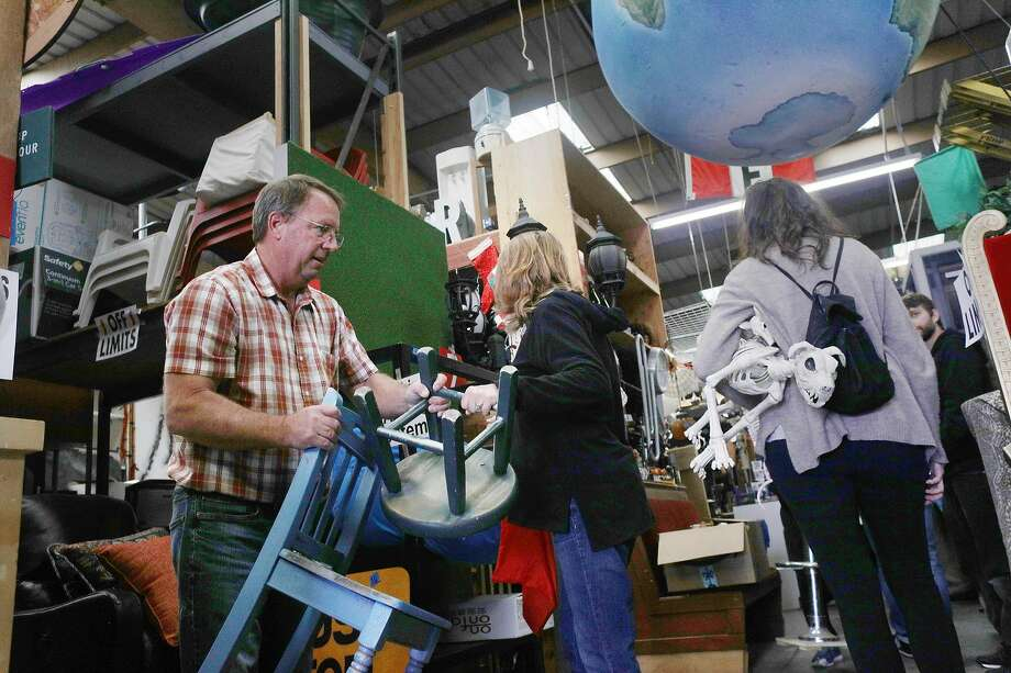 Dirk Dole of Templeton carries different chairs while attending the Acme Scenery and Prop House sale run by YES Company  on Friday, May 17, 2018 in Brisbane, Calif. Photo: Lea Suzuki / The Chronicle