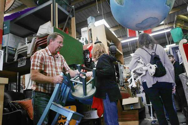 Dirk Dole of Templeton carries different chairs while attending the Acme Scenery and Prop House sale run by YES Company on Friday, May 17, 2018 in Brisbane, Calif.