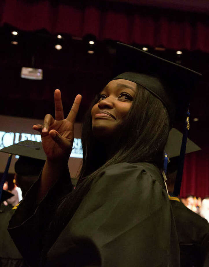 A graduate signals to her guests in the audience during the commencement ceremony inside the Hatheway Cultural Center's Ann Whitney Olin Theatre.