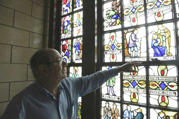 David Lawson, chairman of the Board of Education, points out section of a stained glass window, by Len R. Howard, in the old high school building, now known as the Lillis Administration building. The project was commissioned by the WPA's Federal Arts Program in 1936. New Milford is using a grant to have a consultant study the best way to use the East Street building.