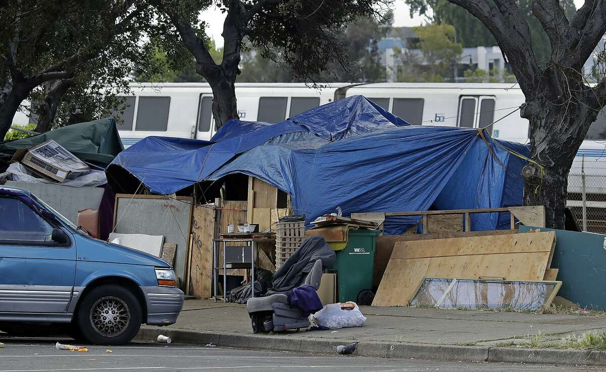 In this file photo, a BART train passes a homeless encampment in Oakland.