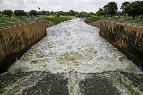 "Water flows down the spillway of the Barker Reservoir dam into Buffalo Bayou. The U.S. Army Corps of Engineers designates both Addicks and Barker dams as ""extremely high risk."""