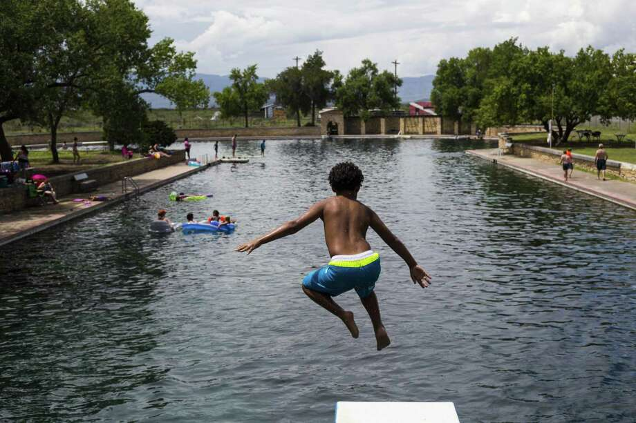 A young boy jumps off the diving board into 30 feet of water at the natural spring pool at the Balmoreah State Park on Thursday, August 18, 2016. The rise of fracking nearby the town has some community members worried about their drinking water and natural springs, which serve as a popular tourism destination helping drive the town's economy. Photo: BRITTANY GREESON, Staff / San Antonio Express-News / © 2016 San Antonio Express-News