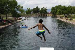 A young boy jumps off the diving board into 30 feet of water at the natural spring pool at the Balmoreah State Park on Thursday, August 18, 2016. The rise of fracking nearby the town has some community members worried about their drinking water and natural springs, which serve as a popular tourism destination helping drive the town's economy.