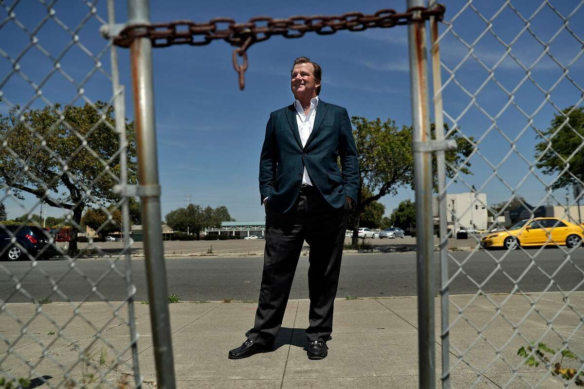 Developer Terry Demmon is seen through the chained gate at the former site of the first Mervyn's department store where he hopes to build a 163-unit combined housing and retail center in San Lorenzo, Calif., on Tuesday, May 7, 2019. Demmons claims the project is being delayed by unions which he claims are trying to force him to use union labor.