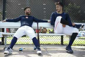 Houston Astros players Jose Altuve, left, and Carlos Correa chat while waiting to take the field for live batting practice at Fitteam Ballpark of The Palm Beaches during spring training.