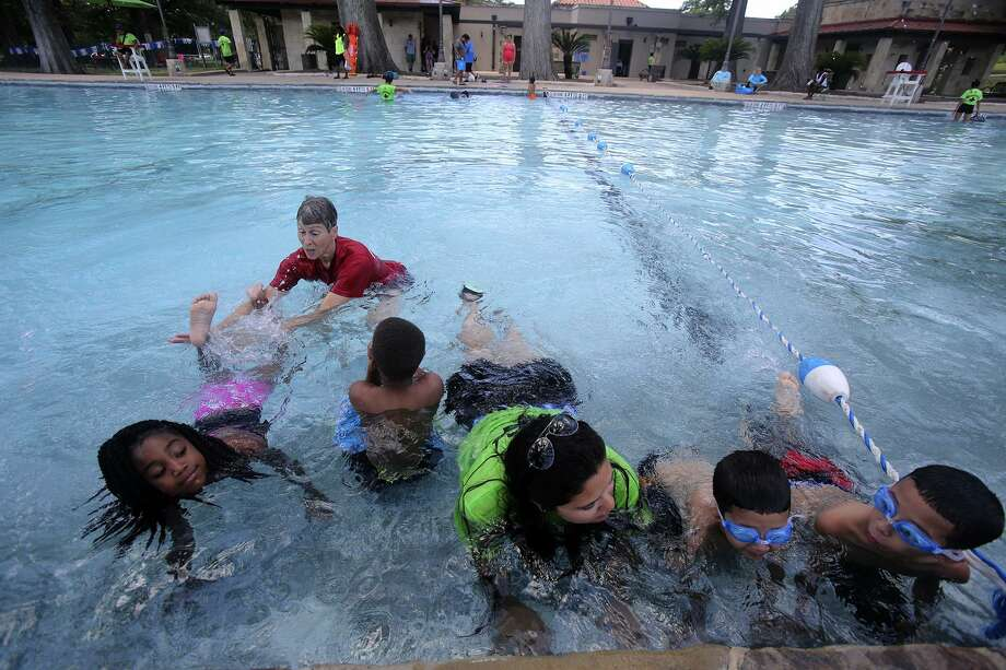 Swimming instructor Elaine Valadez (upper left) and lifeguard Mari Perez (center, with glasses) give swimming lesson on June 21, 2016, at San Pedro Springs Pool after a press conference announcing the start of the San Antonio's summer swim program. Photo: John Davenport /San Antonio Express-News / ©San Antonio Express-News/John Davenport