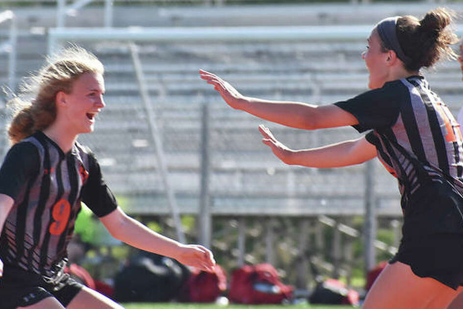 Edwardsville's Payton Federmann, left, celebrates with Brynn Miracle after Miracle scored the game's first goal in the 46th minute against Granite City on Friday in the Class 3A EHS Regional title game.