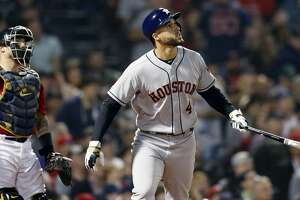 Houston Astros' George Springer (4) watches his two-run home run in front of Boston Red Sox's Christian Vazquez during the eighth inning of a baseball game in Boston, Friday, May 17, 2019. (AP Photo/Michael Dwyer)