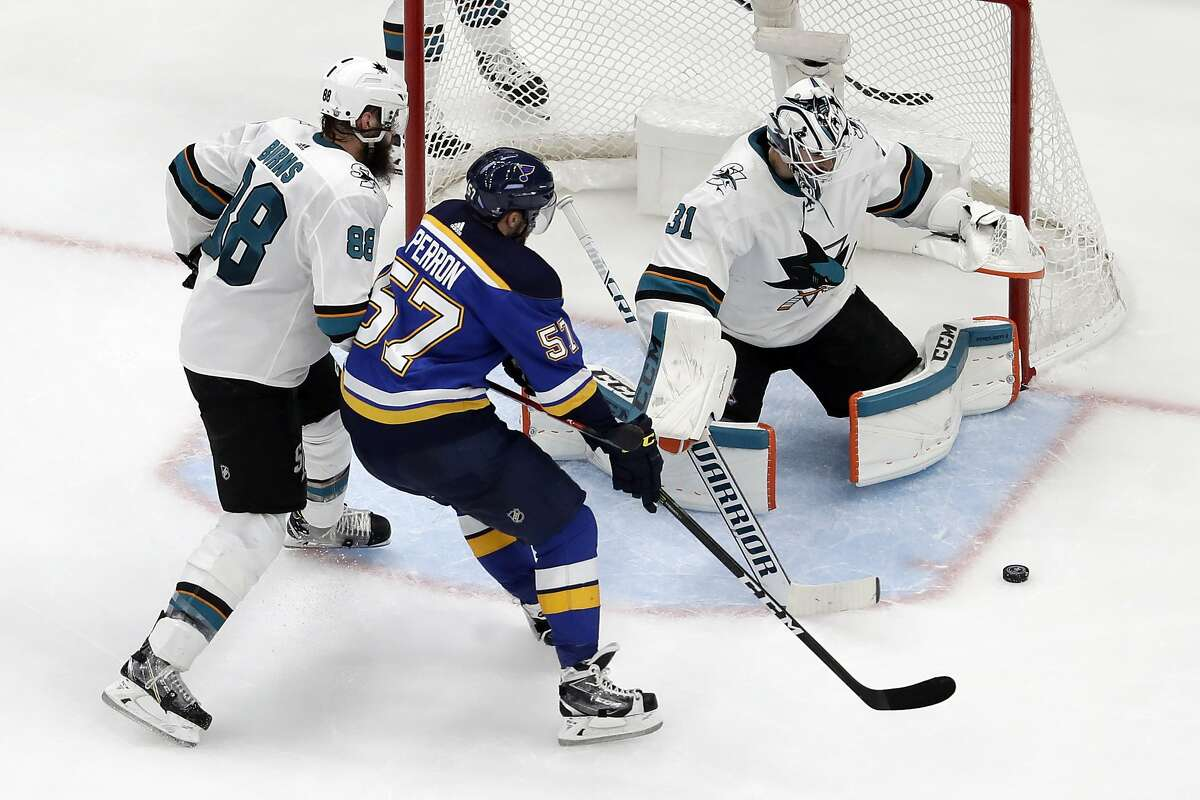 San Jose Sharks goaltender Martin Jones (31) reaches for the puck as St. Louis Blues left wing David Perron (57) closes in during the second period in Game 4 of the NHL hockey Stanley Cup Western Conference final series Friday, May 17, 2019, in St. Louis. Also defending for the Sharks is Brent Burns (88). (AP Photo/Jeff Roberson)