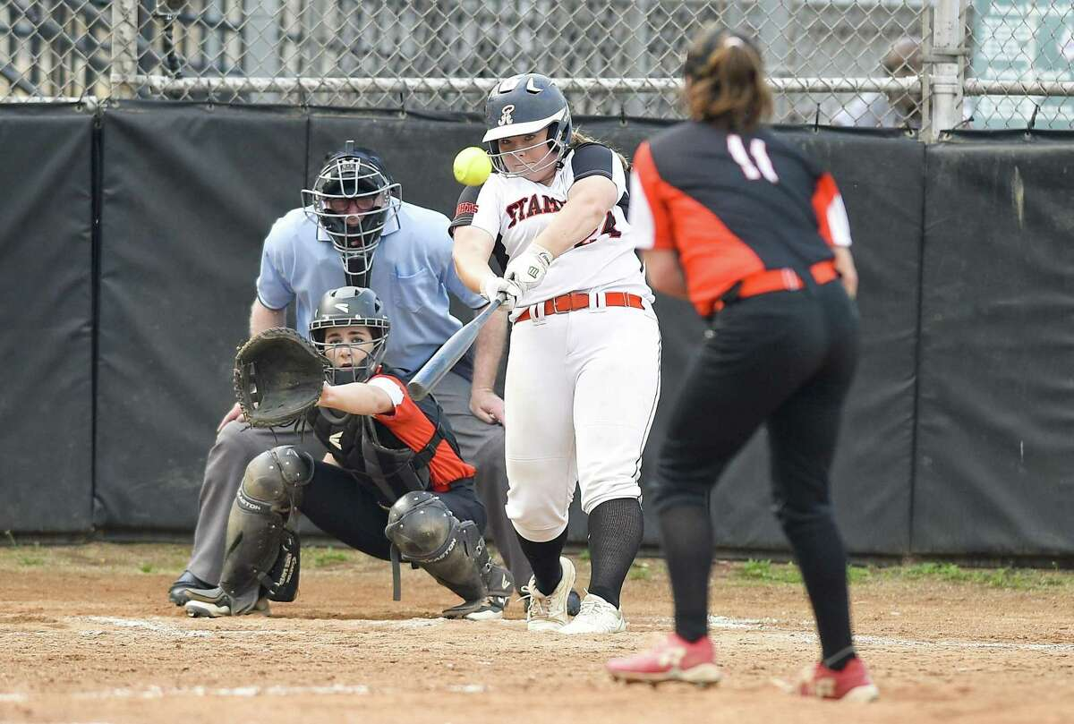 Stamford's Amy Covino (24) crushes a second-inning home run against Ridgfield pitcher Skylar Arent (11) in a FCIAC softball quarterfinal on Friday. Stamford defeated Ridgefield 10-7.