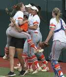 Sam Houston State pitcher Lindsey McLeod, who starred at Austin Westlake, jumps into the arms of her coach and teammates after the Bearkats' victory over Texas on Friday.