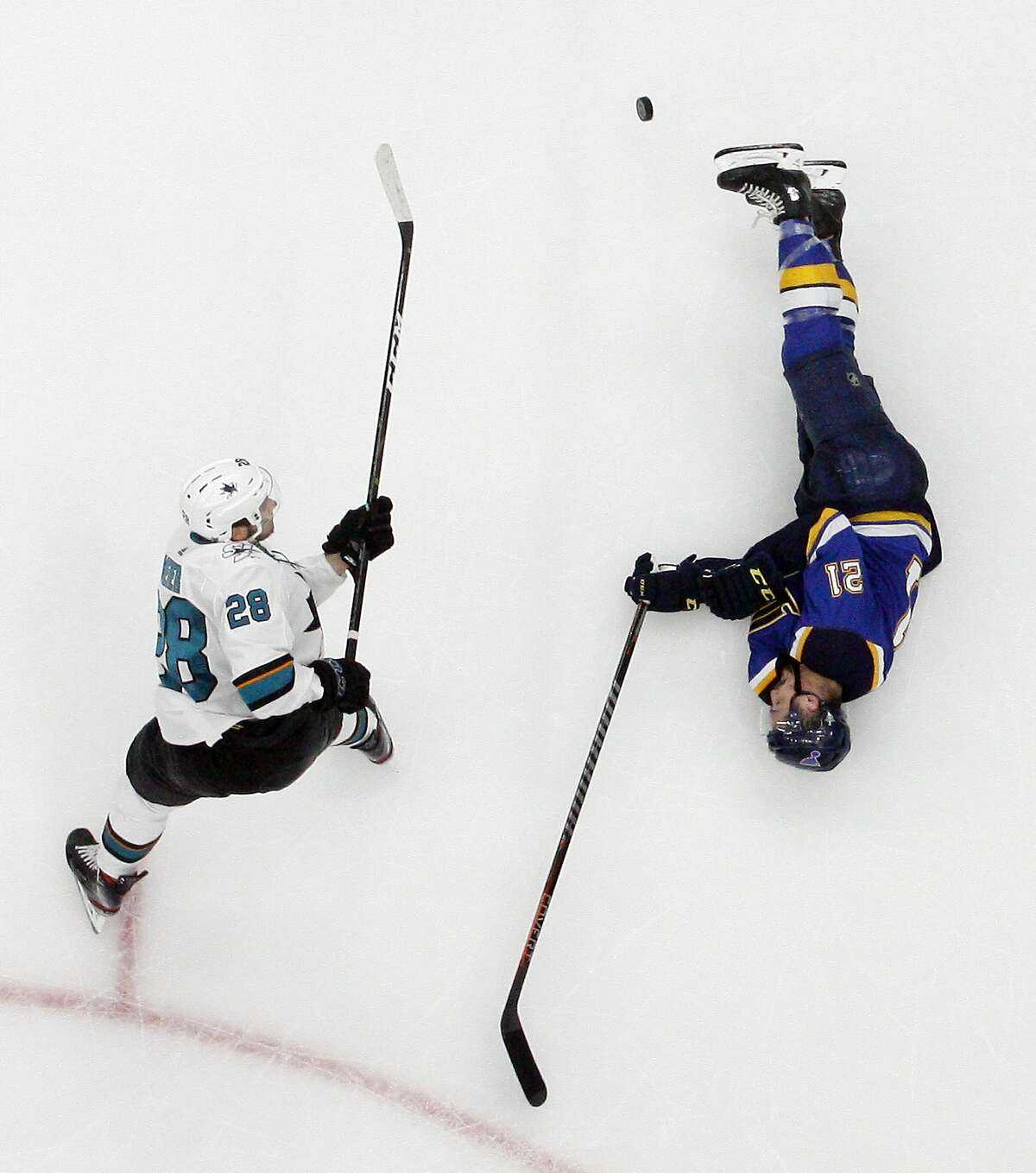 St. Louis Blues center Tyler Bozak (21) slides on the ice to block a shot by San Jose Sharks right wing Timo Meier (28), of Switzerland, during the third period in Game 4 of the NHL hockey Stanley Cup Western Conference final series Friday, May 17, 2019, in St. Louis. The Blues won 2-1 to even the series 2-2. (AP Photo/Jeff Roberson)