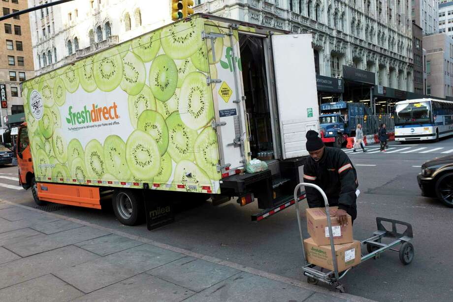 FILE - In this Nov. 27, 2017, file photo a FreshDirect driver loads boxes into his truck in New York.  Grocery delivery services are growing rapidly, but shoppers need to decide if the convenience is worth the higher cost. Big companies like Amazon and Walmart are expanding grocery delivery, as are regional players like FreshDirect. (AP Photo/Mark Lennihan, File) Photo: Mark Lennihan / Copyright 2017 The Associated Press. All rights reserved.