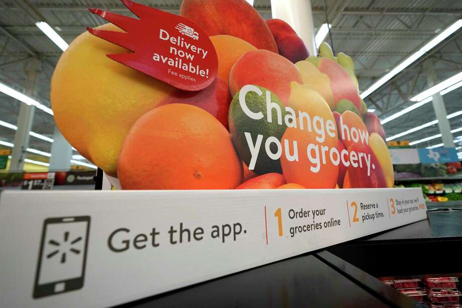 FILE- In this Nov. 9, 2018, file photo a sign promotes online and home delivery of groceries at a Walmart Supercenter in Houston.  Grocery delivery services are growing rapidly, but shoppers need to decide if the convenience is worth the higher cost. Big companies like Amazon and Walmart are expanding grocery delivery, as are regional players like FreshDirect. (AP Photo/David J. Phillip, File) Photo: David J. Phillip / Copyright 2018 The Associated Press. All rights reserved.