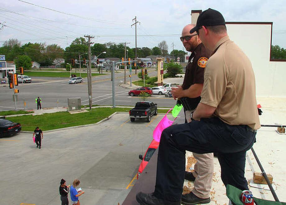Illinois Department of Corrections officers and members of other area law enforcement agencies participated in the Cop on a Rooftop event to benefit the Law Enforcement Torch Run for Special Olympics. Officers stood on the roof of Dunkin' Donuts in Jacksonville from 5 a.m. to noon Friday. Photo: Rosalind Essig | Journal-Courier
