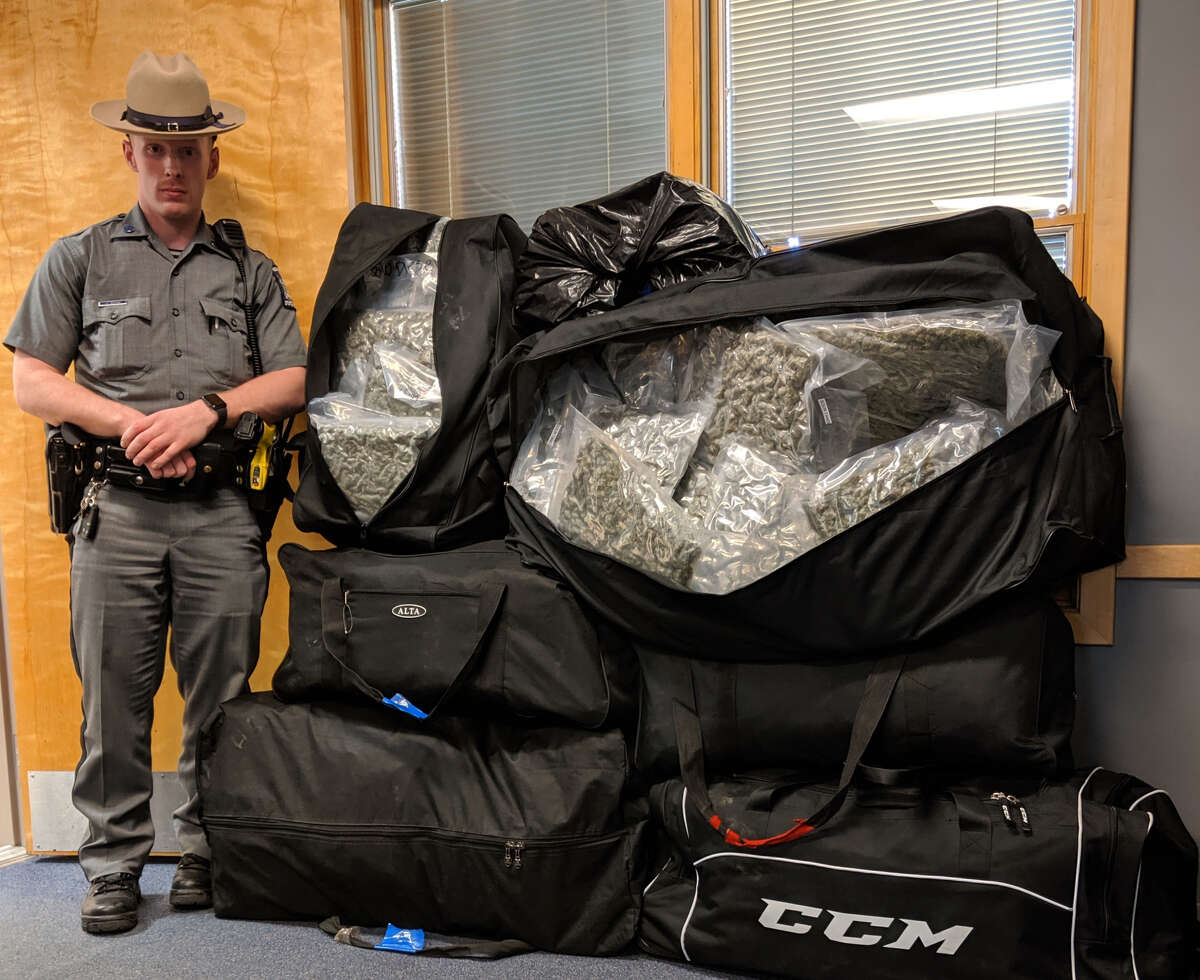 A state trooper based on the Thruway stands next to 200 pounds of marijuana seized from a car in Chatham.