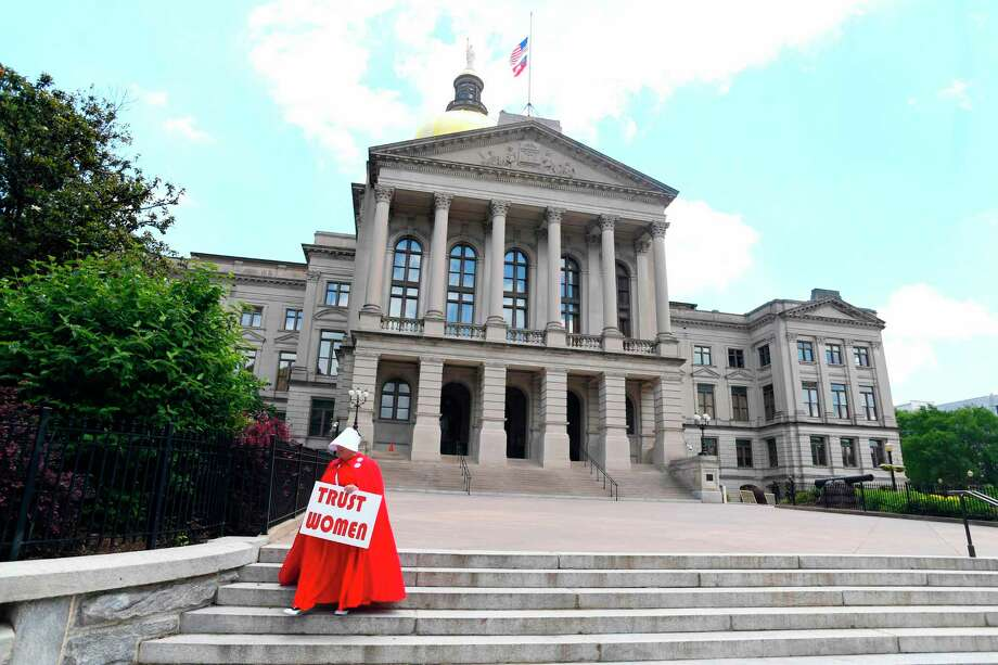 """TOPSHOT - Activist Tamara Stevens with the Handmaids Coalition of Georgia leaves the Georgia Capitol after Democratic presidential candidate Sen. Kirsten Gillibrand (D-NY) addressed an event to speak out against the recently passed """"heartbeat"""" bill on May 16, 2019 in Atlanta, Georgia. - The bill, which bans abortions after a fetal heartbeat is detected around six weeks, was signed on May 15 by Alabama Governor Kay Ivey. Under the new measure, expected to come into effect in six months, performing an abortion is a crime that could land doctors in prison for up to 99 years. (Photo by John Amis / AFP)JOHN AMIS/AFP/Getty Images Photo: JOHN AMIS / AFP or licensors"""