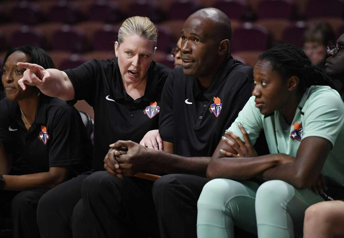 New York Liberty head coach Katie Smith, left, talks with assistant coach Herb Williams during the second half of a preseason WNBA game Tuesday in Uncasville.