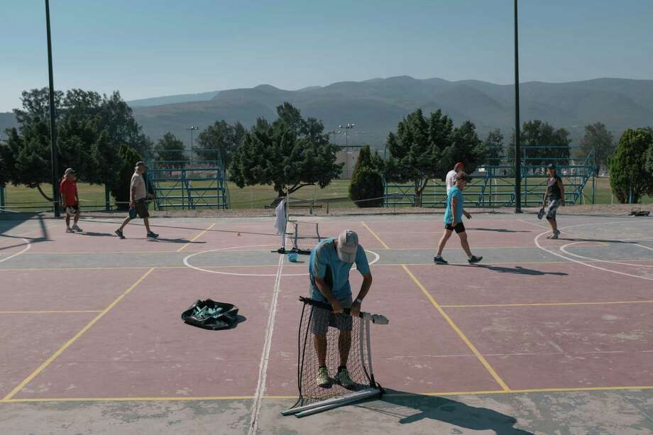 A man folds a pickleball net in San Miguel de Allende, Mexico. American retirees gather at the municipal sports center several days a week to play the sport favored by seniors in the United States. Photo: Photo For The Washington Post By Luis Antonio Rojas / Luis Antonio Rojas
