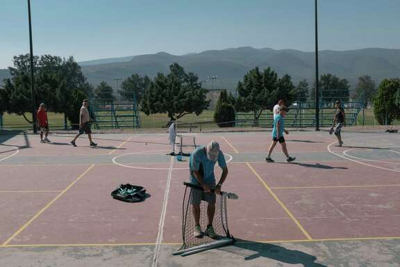 A man folds a pickleball net in San Miguel de Allende, Mexico. American retirees gather at the municipal sports center several days a week to play the sport favored by seniors in the United States.