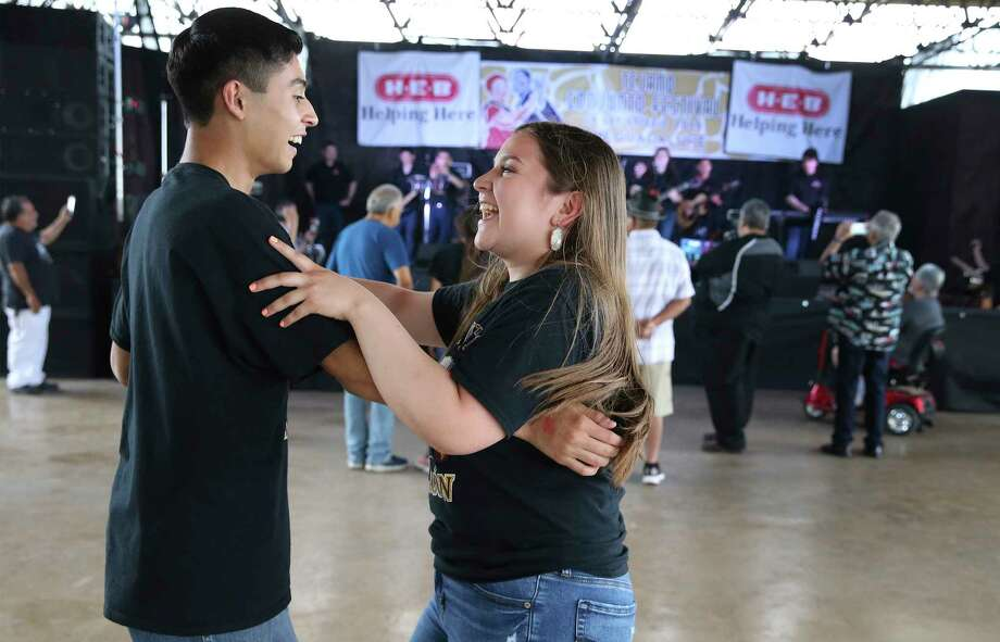 Barbara Canales (right) and Michael Huerta of Conjunto Halcon in Los Fresnos, Texas enjoy a dance as the Guadalupe Cultural Arts Center hosts the annual Tejano Conjunto Festival at Rosedale Park on Saturday, May 18, 2019. The musical and cultural event is now in its 38th year and considered the longest running celebration of conjunto music in the country. The festival features an ever-growing list of performances not only by the top acts in the genre but also with a showcase of performances by students from local and area schools. Highlights of the five-day long event included an induction ceremony into the Conjunto Hall of Fame which included: Pepe Maldonado, Lorenzo Martinez, Norfy Layton and Edgar Vasquez. On Saturday, despite a light rain, high school students from the Rio Grande Valley were the first to take the stage under a pavilion that shielded them from the weather. Accordions, guitars and vocalists echoed throughout the park and whipped up the crowd to take the dance floor. The event runs through Sunday with acts starting at noon and going through 10 p.m. Admission is $16 per person. (Kin Man Hui/San Antonio Express-News) Photo: Kin Man Hui, Staff Photographer / ©2019 San Antonio Express-News