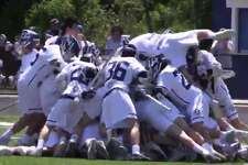 Wilton celebrates its 4-3 overtime win over Staples in the FCIAC boys lacrosse quarterfinals at Fujitani Field in Wilton on May 18, 2019.