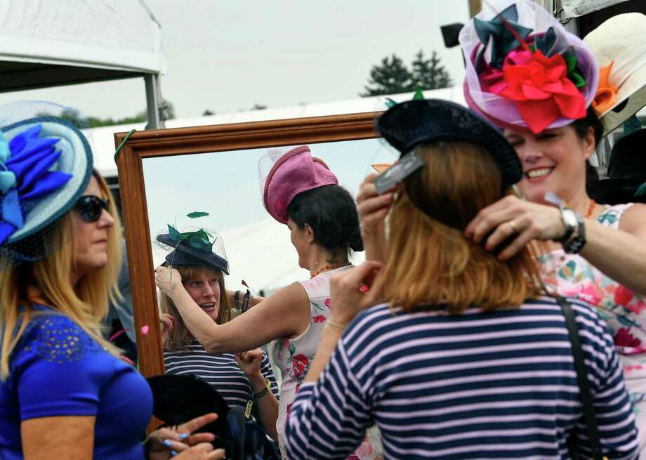 Kerry Carlson is helped by Christine Moore as she tries on one of Moore's hats from her millinery booth at Pimlico Race Course ahead of the 144th Preakness Stakes in Baltimore. Photo: Washington Post Photo By Toni L. Sandys / The Washington Post