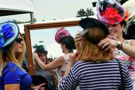 Kerry Carlson is helped by Christine Moore as she tries on one of Moore's hats from her millinery booth at Pimlico Race Course ahead of the 144th Preakness Stakes in Baltimore.