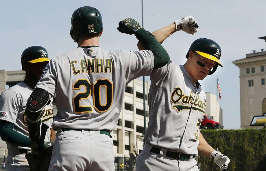 A's catcher Nick Hundley (right) is congratulated by Mark Canha (20) after he blasted a two-run home run, Hundley's first homer of the season, during the third inning. Chad Pinder also hit a home run in the seventh in Detroit, and the A's 39 homers on the road is fourth most in the league. Photo: Carlos Osorio / Associated Press