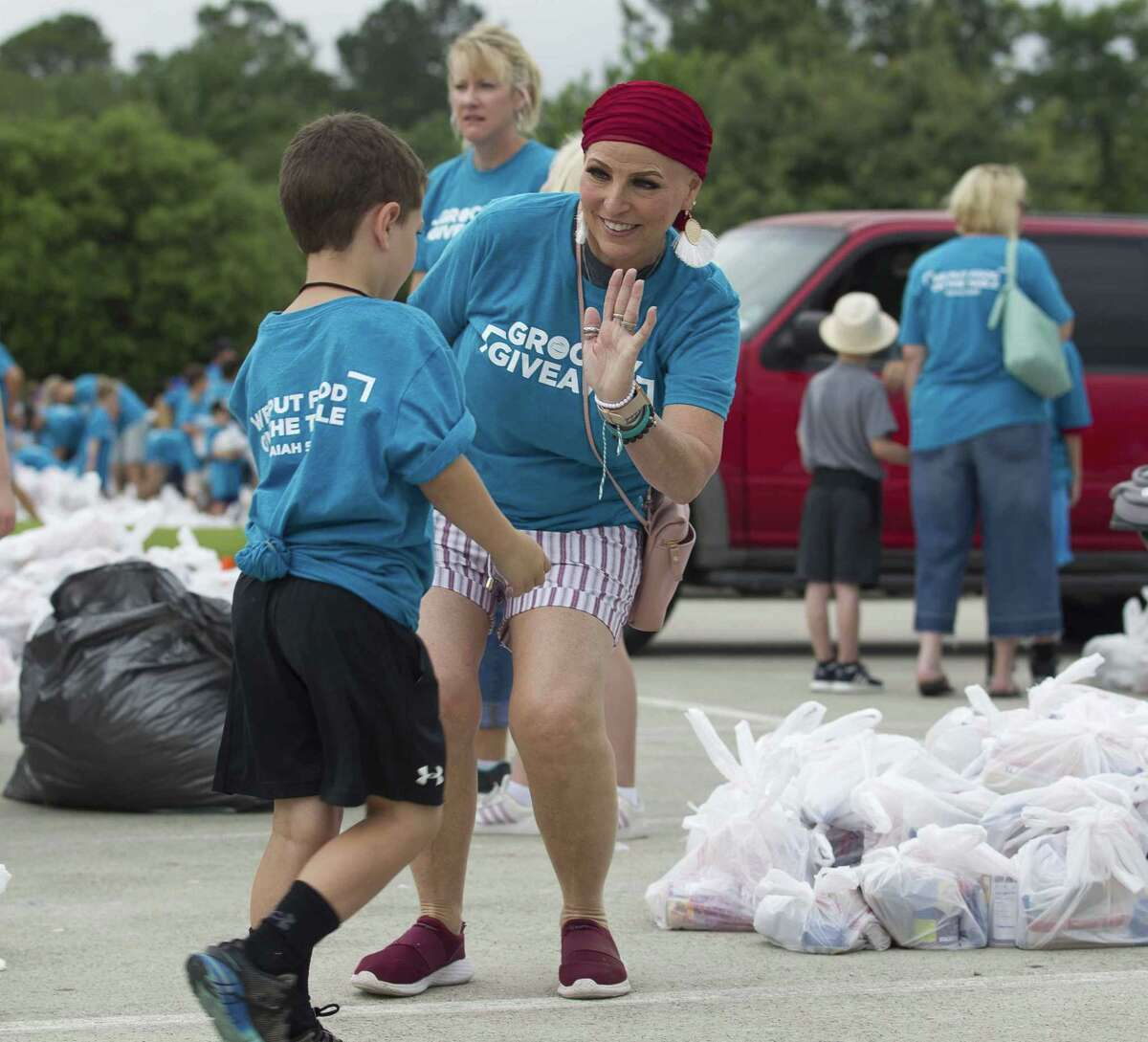 Vickie Ruiz gives high-fives during The Ark Church's annual spring giveaway that provided food for Montgomery County residents in need, Saturdayin Conroe.