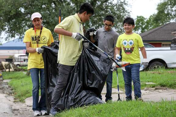 Margarita Arellano, from left, Armando Garcia, 16, his brother Fernando Garcia, 16, and Christian Montoya, 11, work to clean trash and debris from gutters in the neighborhood surrounding Lake Forest Park on Saturday, May 18, 2019, in Houston.