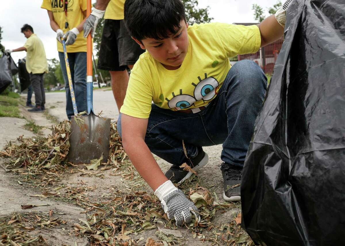 Christian Montoya, 11, works to clean leaves and trash from a gutter to improve drainage on Saturday, May 18, 2019, in Houston.