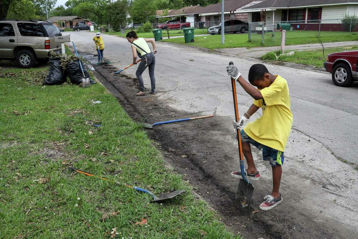 Na'shoun Charent, 12, works to clean a gutter on his street, Kellett Street, to improve drainage in the area on Saturday, May 18, 2019, in Houston. Clarent said his home flooded during Hurricane Harvey.