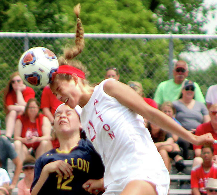 Tori Schrimpf of Alton (21) heads the ball away from O'Fallon's Sydney Christopher in Saturday's championship game of the Alton Class 3A Regional Soccer Tournament at Alton High. O'Fallon won 2-0. Photo: Pete Hayes | The Telegraph