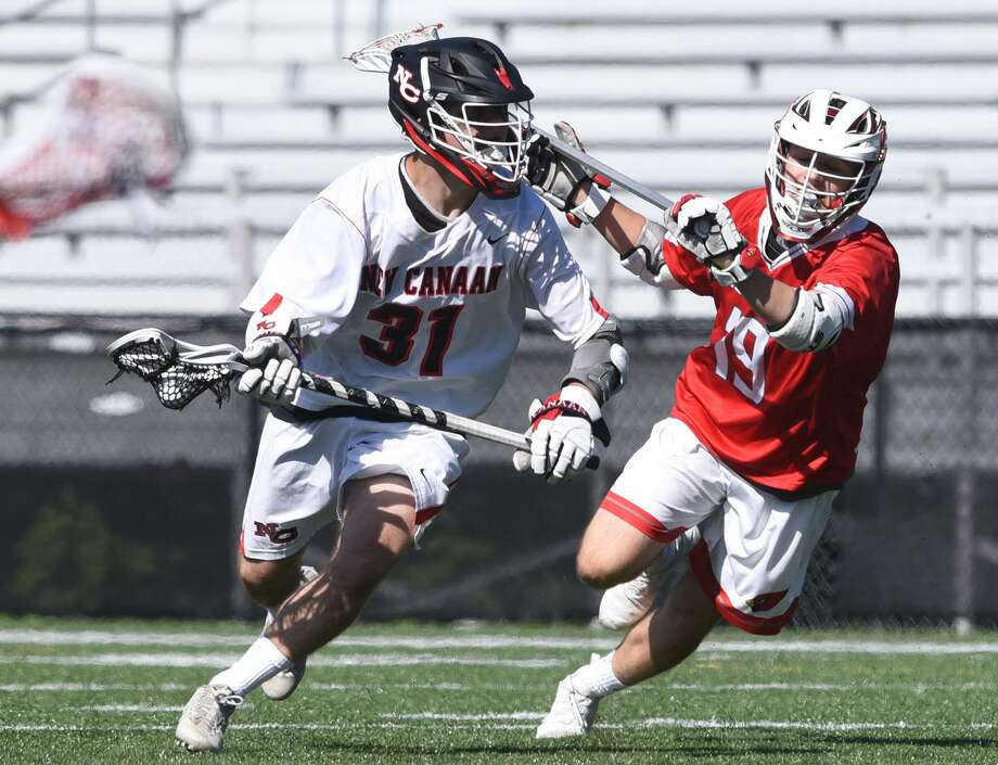 New Canaan's Ryan Caione (31) drives past Greenwich's Jason Tautel (19) on Saturday. Photo: Dave Stewart / Hearst Connecticut Media / Hearst Connecticut Media