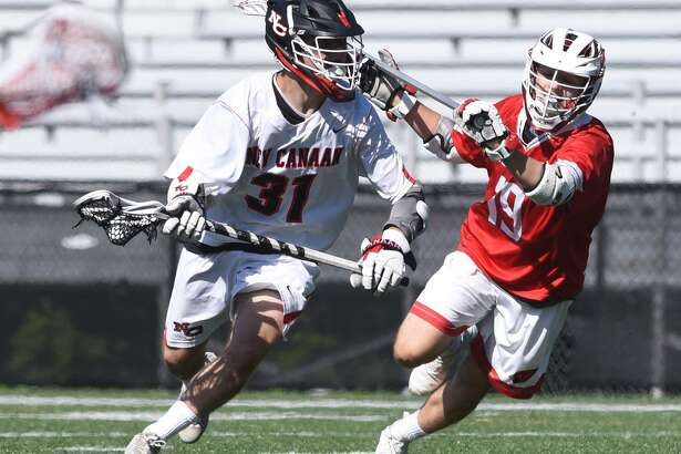New Canaan's Ryan Caione (31) drives past Greenwich's Jason Tautel (19) on Saturday.