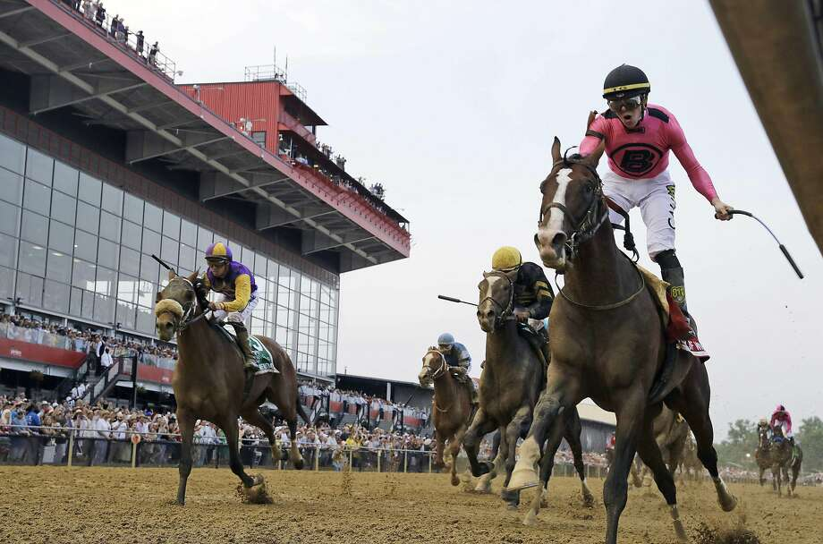 Jockey Tyler Gaffalione (right) reacts aboard War of Will as they cross the finish line first to win the Preakness Stakes. Photo: Steve Helber / Associated Press