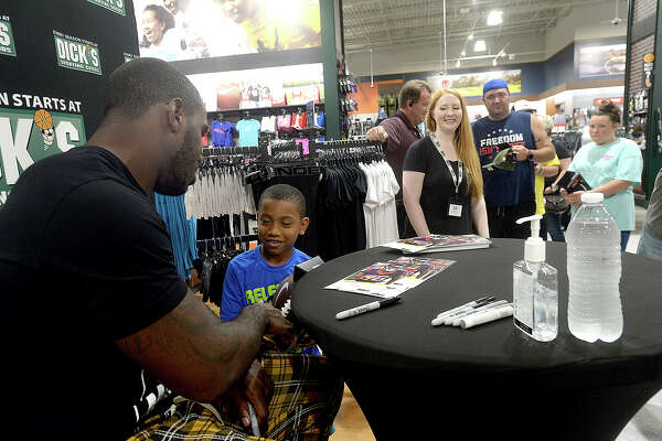 Texans running back Lamar Miller autographs memorabilia for fans Saturday at the newly opened Dick's Sporting Goods store in Beaumont. The event was part of the store's grand opening weekend celebration. Photo taken Saturday, May 18, 2019 Kim Brent/The Enterprise
