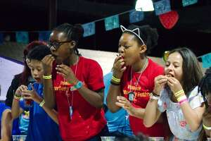 Nick Nguyen, Kayden Kelley, Mylaneah Kelley and Kinleigh Mackey compete in the Pasadena Strawberry Festival strawberry eating contest Saturday, May 18.