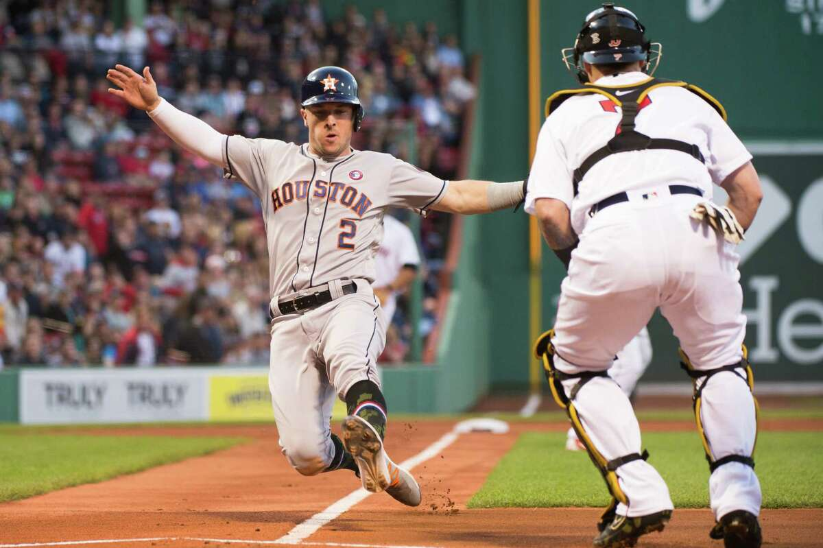 BOSTON, MA - MAY 18: Alex Bregman #2 of the Houston Astros safely slides into home plate in the first inning against the Boston Red Sox at Fenway Park on May 18, 2019 in Boston, Massachusetts.