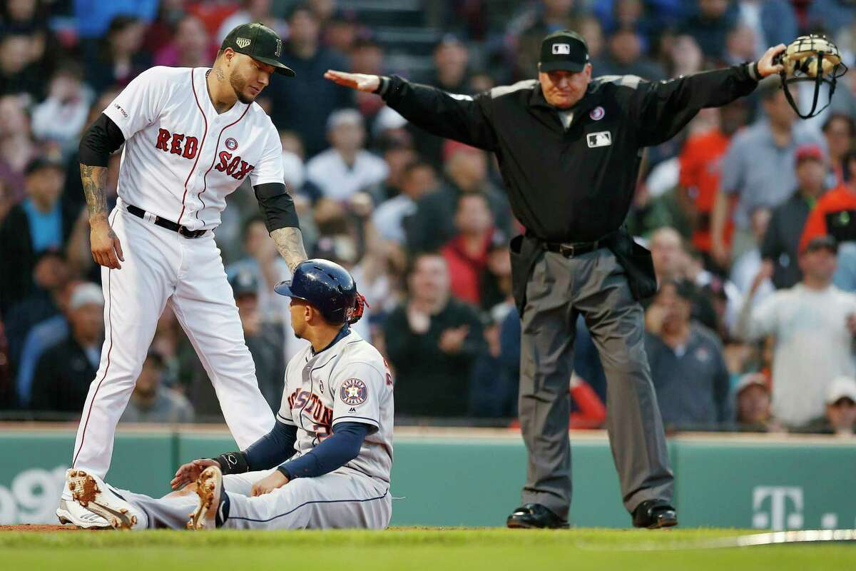 """Home plate umpire Jeff Nelson signals """"Safe"""" as Houston Astros' Michael Brantley, center, looks up at Boston Red Sox's Hector Velazquez, left, after scoring on a single by Yuli Gurriel during the first inning of a baseball game in Boston, Saturday, May 18, 2019. (AP Photo/Michael Dwyer)"""