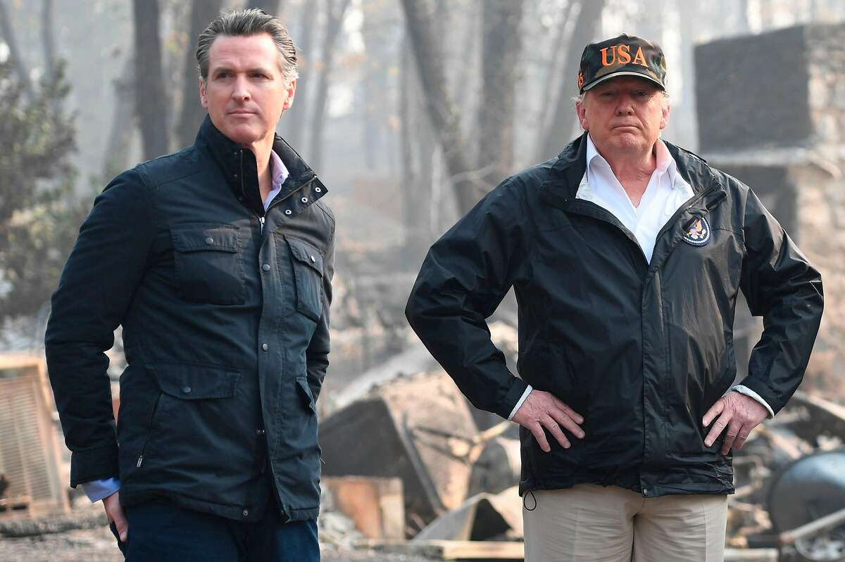 US President Donald Trump looks on with Lieutenant Governor of California, Gavin Newsom, as they view damage from wildfires in Paradise, California on November 17, 2018. Newsom recently announced his intention to withdraw most of California's National Guard troops from the border, saying the state needs tUS President Donald Trump (C) looks on with Governor of California Jerry Brown (R) and Lieutenant Governor of California, Gavin Newsom, as they view damage from wildfires in Paradise, California on November 17, 2018. The Trump administration cancelled nearly $1 billion in federal funds for California's high-speed rail project. California Gov. hem to prepare for wildfires and to fight drug trafficking. (Photo credit should read SAUL LOEB/AFP/Getty Images)