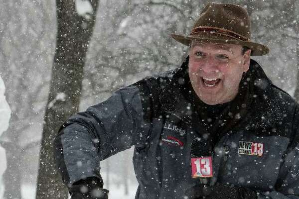 Many people know me for my Stetson hat. I began wearing it one Thanksgiving Eve, when I had to cover a snow storm. Telling others to dress warmly meant I should too. It's become a staple ever since. (Photo H: Covering a snow storm in Washington Park. Photo by Skip Dickstein)