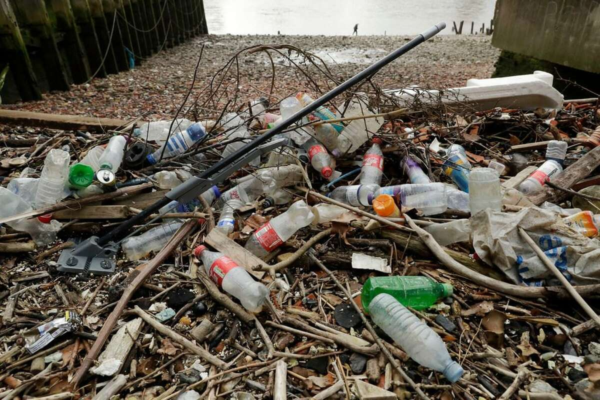 Plastic bottles and other plastic products, including a mop, lie washed up on the shore at the site of the ancient Queenhithe dock on the north bank of the River Thames in London. Almost every country in the world has agreed on a binding framework for reducing plastic waste, with the United States a notable exception, United Nations environmental officials said.