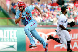 The Cardinals' Paul DeJong (12) sprints around the bases, scoring on a Jose Martinez single as Texas Rangers' Danny Santana moves to cover second in the fifth inning Saturday's game in Arlington, Texas.